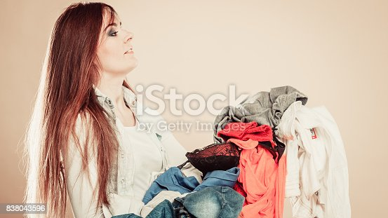 460589747istockphoto Side view young woman hold pile of clothes. 838043596