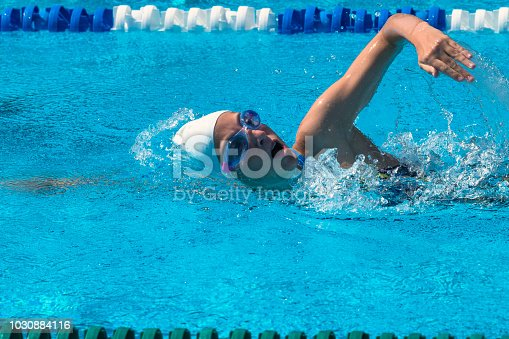 Side view of teenager at freestyle swimming outdoors
