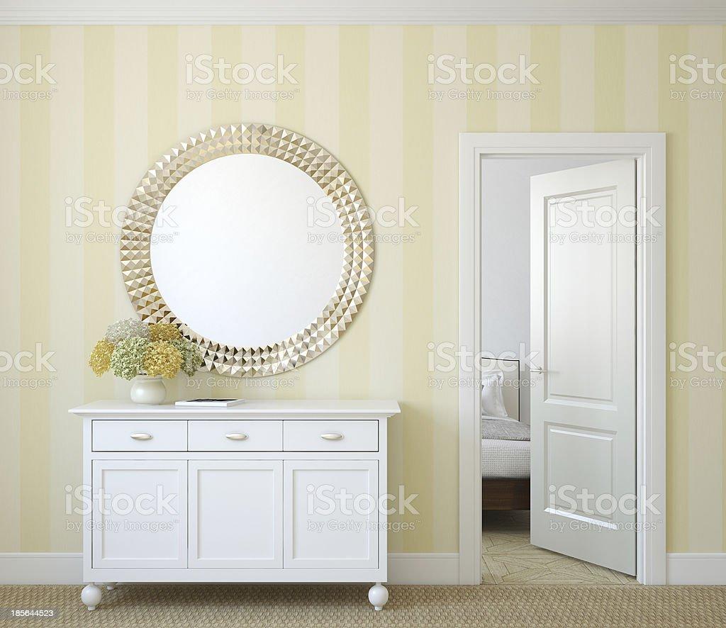 Sideboard and mirror in yellow hallway with open door stock photo