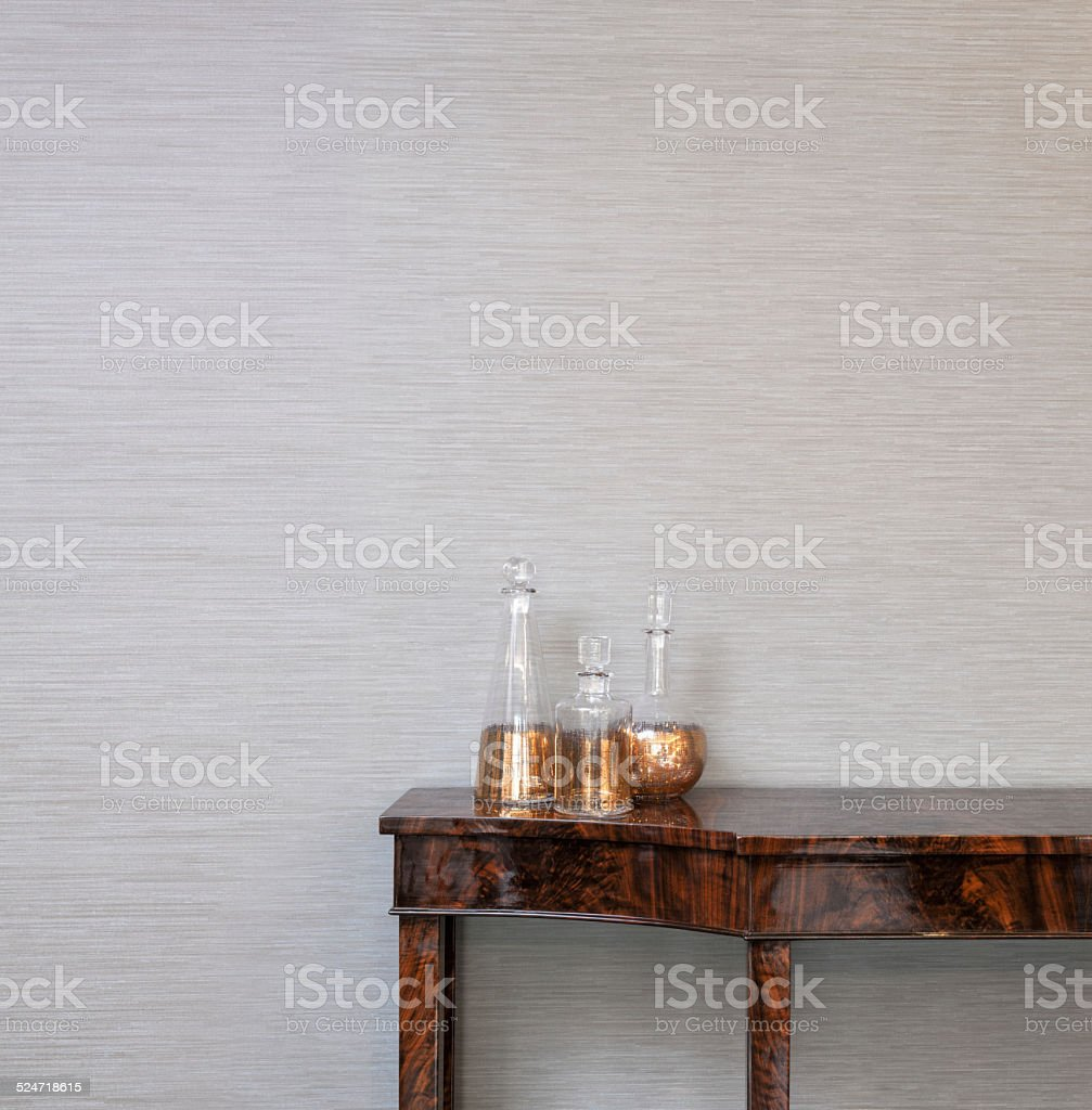 Sideboard in front of a grey wall with whiskey bottle stock photo