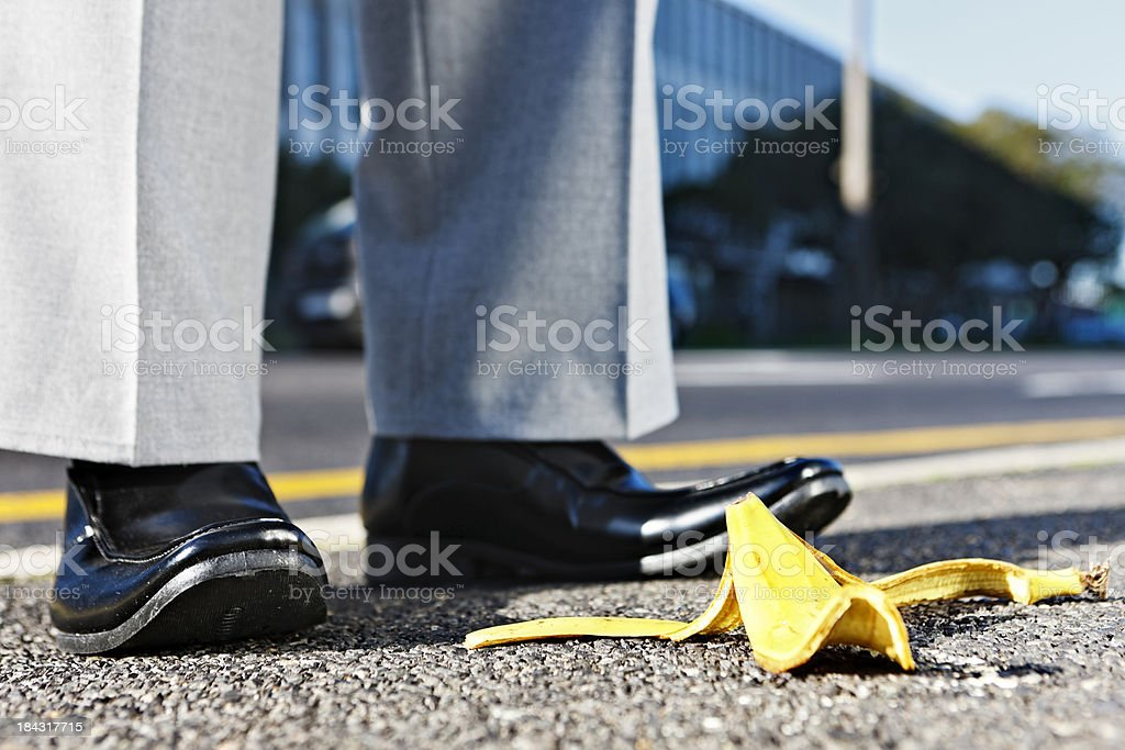 Sidestepping a problem: businessman's feet next to banana peel royalty-free stock photo