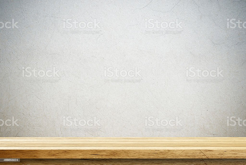 A sideview image of a wooden table against a cement wall stock photo