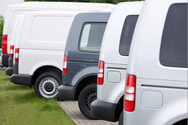 sideview of new vans in a row - sale stok fotoğraflar ve resimler