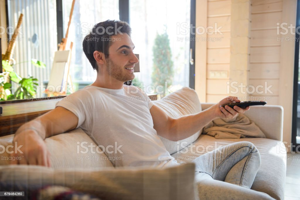Sideview of sitting on couch man with remote controller royalty-free stock photo