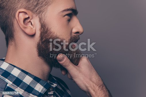 istock Side-view portrait of thinking stylish young man touch his beard 636830758