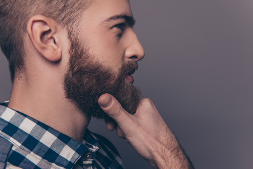 636829368 istock photo Side-view portrait of thinking stylish young man touch his beard 636830758
