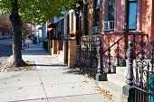A neighborhood sidewalk next to a row of old homes in Greenpoint Brooklyn New York