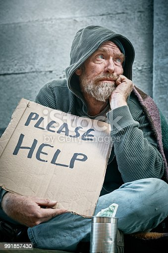 883034410 istock photo Sidewalk beggar looks to Heaven for help 991857430