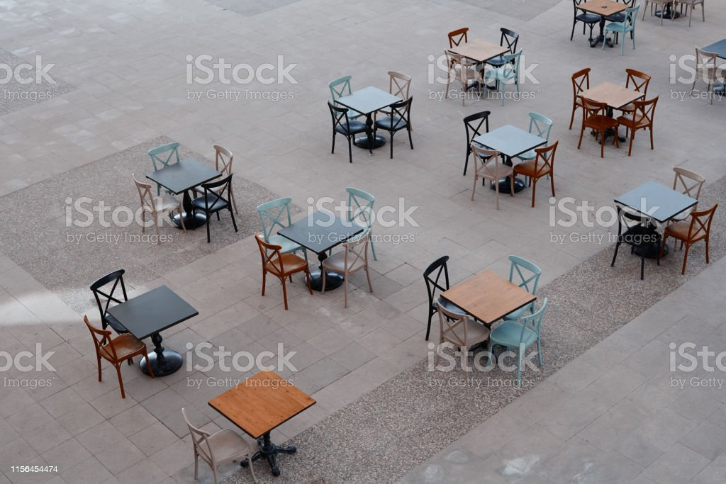 Sidewalk cafe chairs and tables in a row from high angle