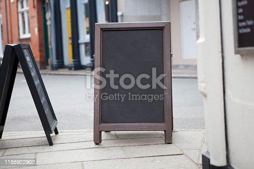 628470570 istock photo Sidewalk chalkboard street sign 1155922902