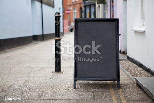628470570 istock photo Sidewalk chalkboard street sign 1155923169