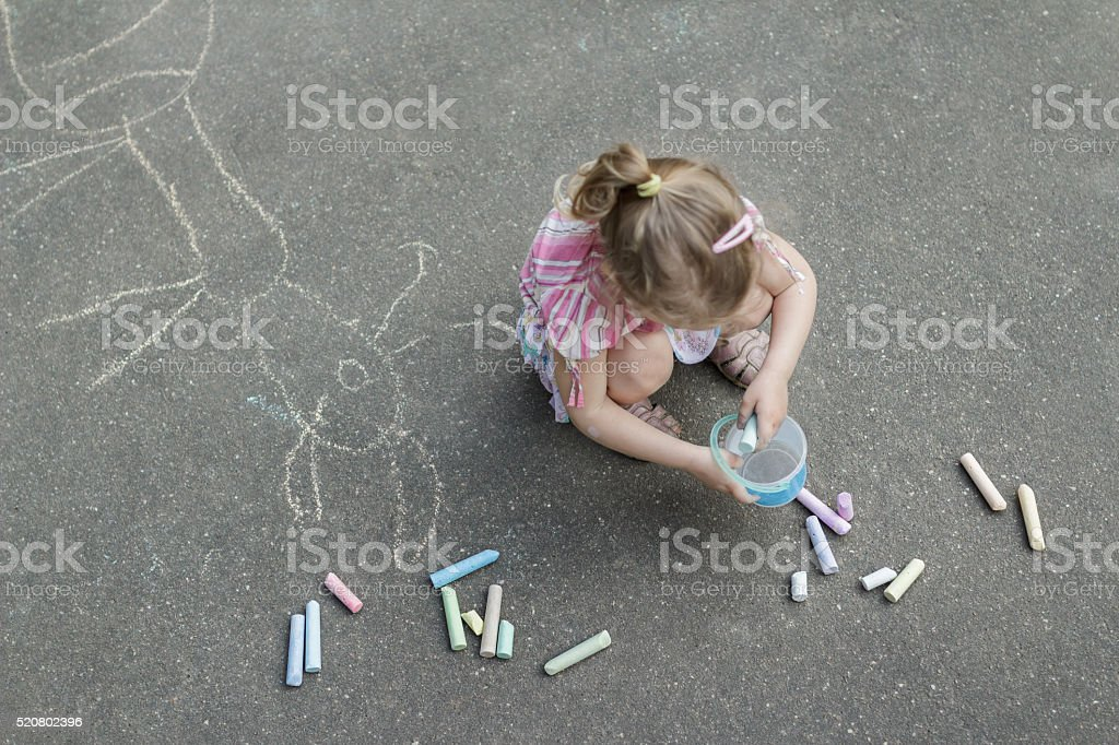 Sidewalk chalking of little blonde girl wearing pink ruffle skirt stock photo