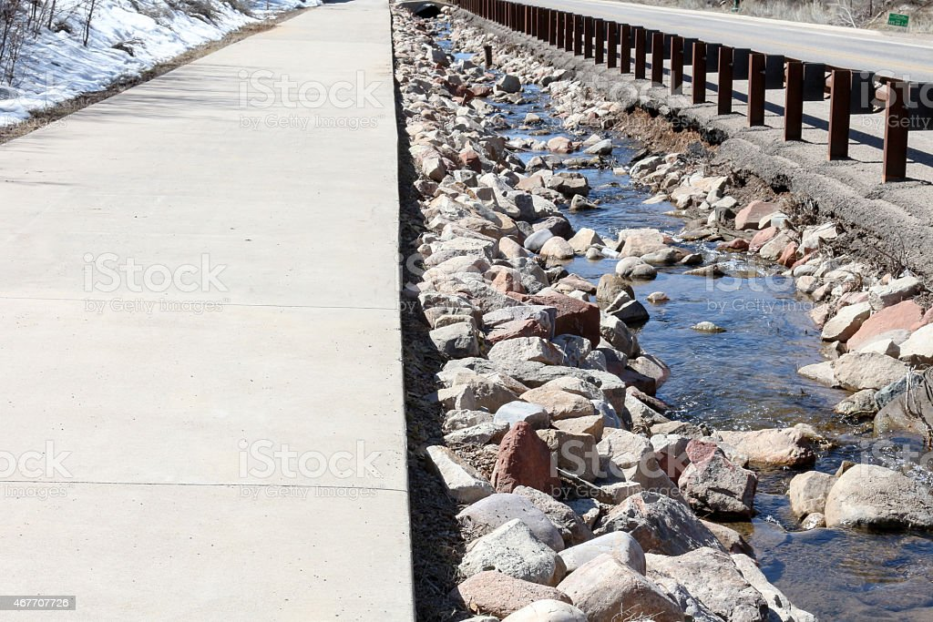 Sidewalk, drainage ditch and road vanishing point stock photo