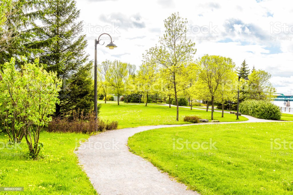 Sidewalk in green downtown city park in Saguenay, Canada, Quebec during summer with fjord river, bridge, boardwalk promenade stock photo