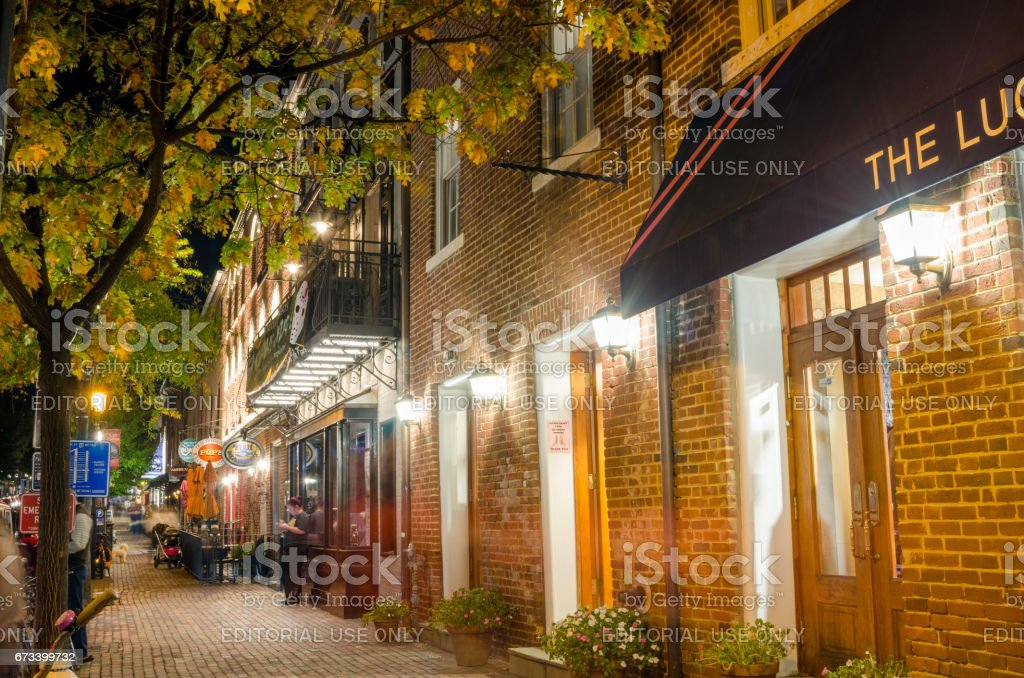 Sidewalk lined with Restaurants and Shops in Old Town Alexandria, VA, at Night stock photo