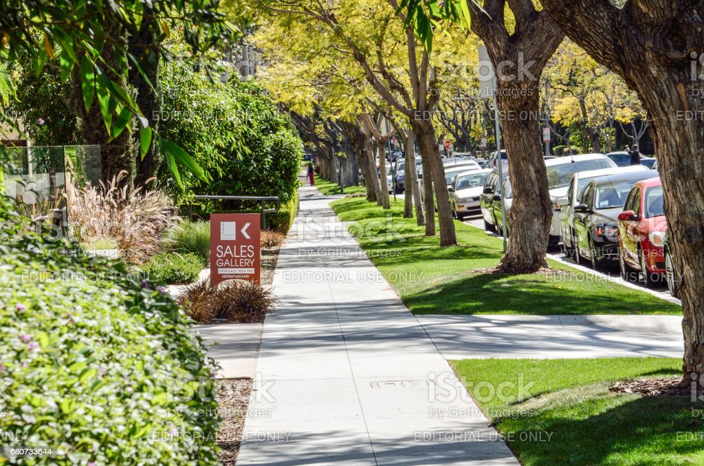 Sidewalk on street in downtown LA in Beverly Hills with residential houses and trees with sales gallery sign stock photo