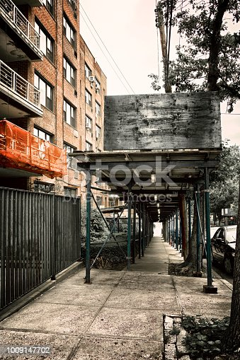 As a building's exterior is being repaired, New York City law requires that a Sidewalk Overhead Protection Scaffold be constructed for the protection of pedestrians passing by. These structures are also called a
