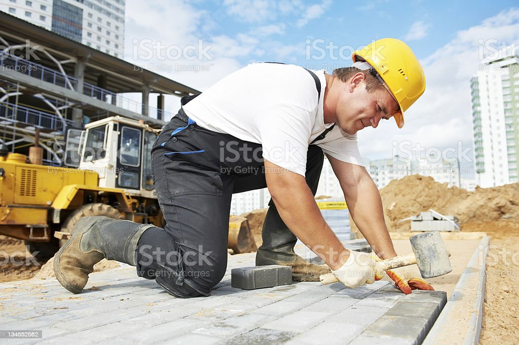 sidewalk pavement construction works mason worker making sidewalk pavement with stone blocks Activity Stock Photo