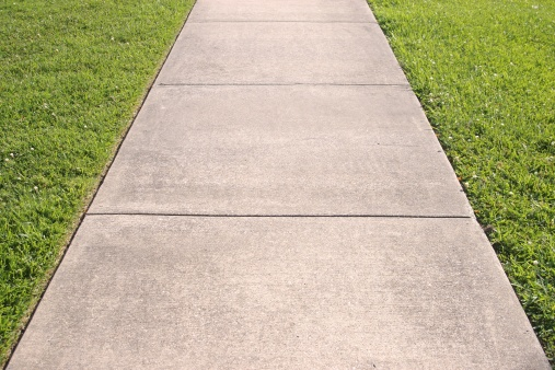 a concrete sidewalk with grass on both sides
