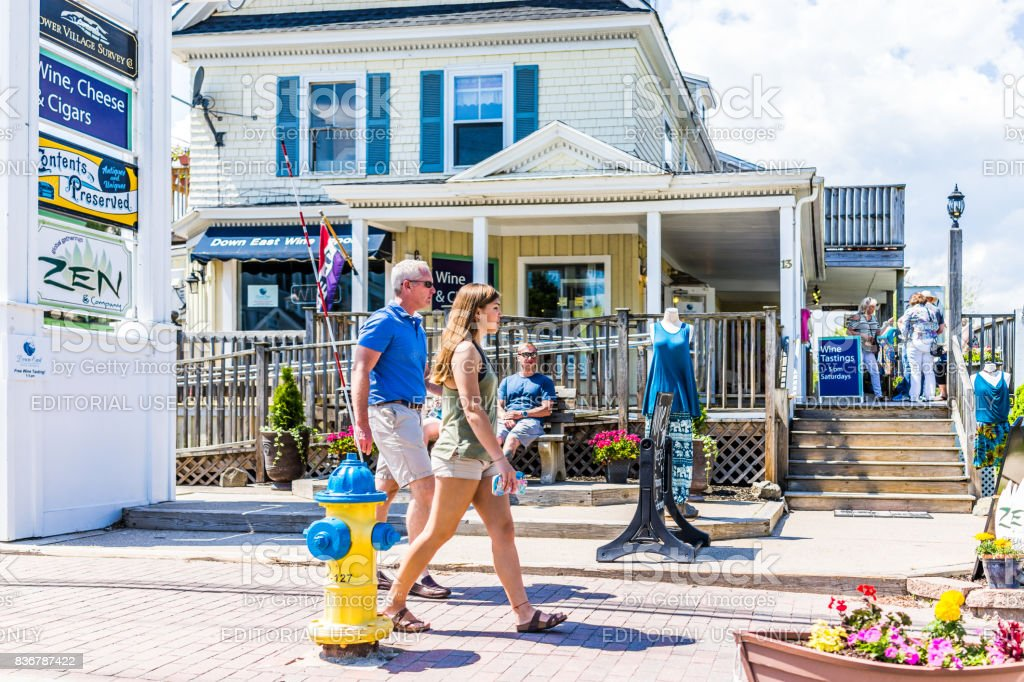 Sidewalk street with people walking by mall in downtown village during summer day stock photo