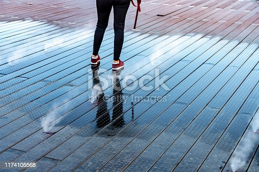 Sidewalk water vapour spouts in Lyon. an unrecognizable tourist is walking over the spouts in the pavement made up of water jets which spray alternatively water and mist to create a fog like appearance.