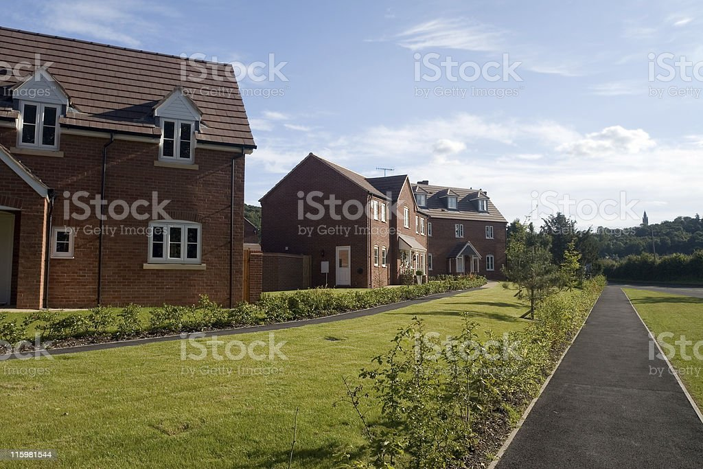 Sidewalk with nicely manicured landscape and brick houses royalty-free stock photo
