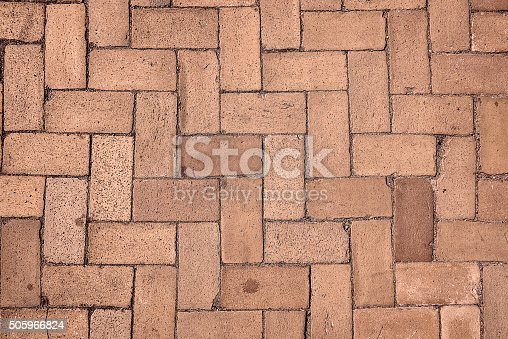 Elevated view of a textured brick sidewalk with a red and yellow color. The sidewalk has a zig-zag pattern and is rough to look at.