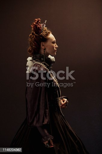 Queen Elizabeth I concept. The woman portraying her is dressed traditionally, smiling at the camera in front of a back studio background with her hands in her pockets providing a modern twist.