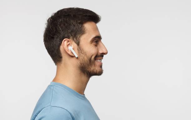sur le côté portrait de jeune homme, écouter de la musique ou la radio, souriant utilise des écouteurs sans fil modernes, portant le t-shirt bleu. espace copie de texte - écouteurs intra auriculaires photos et images de collection
