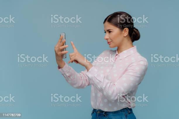 Sideways shot of brunette lady has combed hair holds modern cell picture id1147782709?b=1&k=6&m=1147782709&s=612x612&h=slfll9ahep8uh4j8msbc5eebl2grxoudq3a1lra1suu=