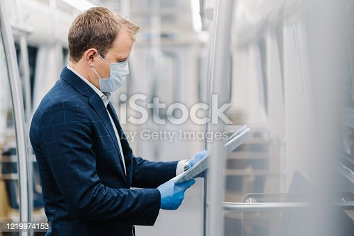 Sideways shot of young elegant man reads newspaper attentively, poses in metro carriage, wears medical mask and disposable rubber gloves from coronavirus. Social distancing, quarantine measures