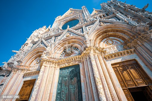 Wide angle image showing the Intricately carved marble and ornate entrance doors on the ancient facade of Siena Cathedral in Tuscany, Italy.