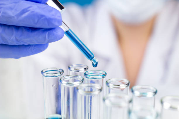sientist with pipette blue water drop in test tubes in laboratory. - laboratory glassware stock pictures, royalty-free photos & images