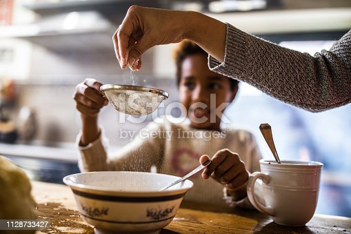 Close up of unrecognizable woman sieving flour with her daughter in the kitchen.