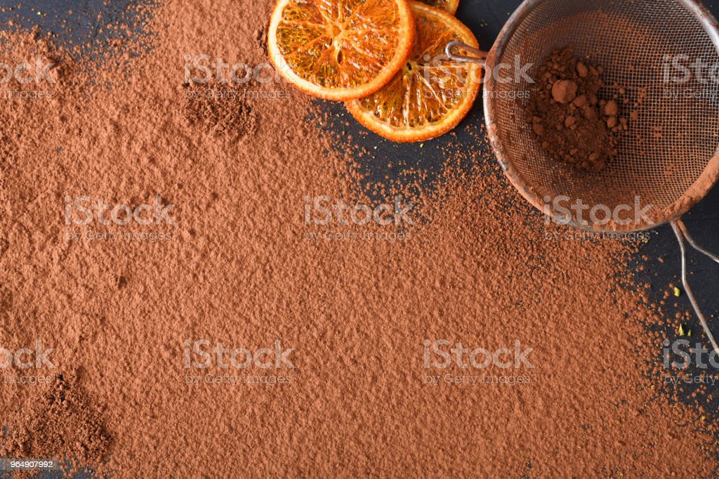 Sifted cocoa powder in a sieve over black background royalty-free stock photo