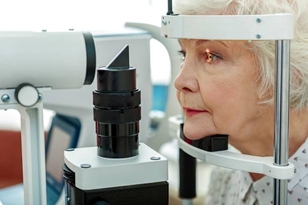 sight of old woman verifying by apparatus - investigating eye bildbanksfoton och bilder