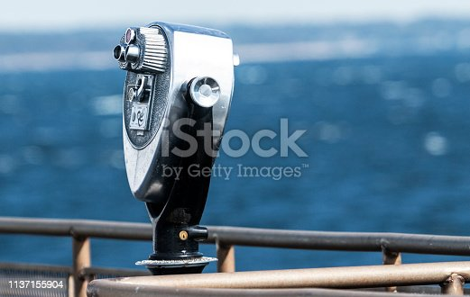 A boat has a michanical sightseeing binoculars for tourists to see distant objects up close.