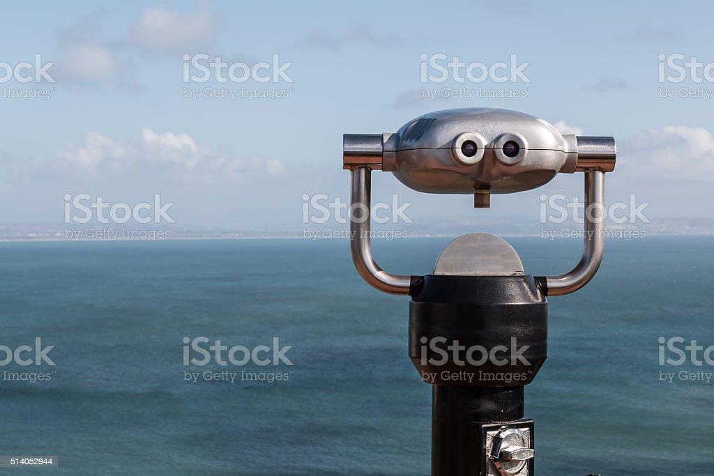 Sightseeing Binoculars Overlooking Ocean From Up High Sightseeing binoculars overlooking the ocean from a high vantage point Binoculars Stock Photo