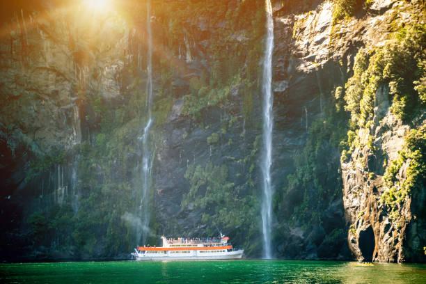 Sightseeing-Boot mit touristischen Menschen nähert sich großen Wasserfall in Milford Sound. Landschaftlich schöne Kreuzfahrt durch Fiordland-Nationalpark auf der Südinsel Neuseelands. – Foto