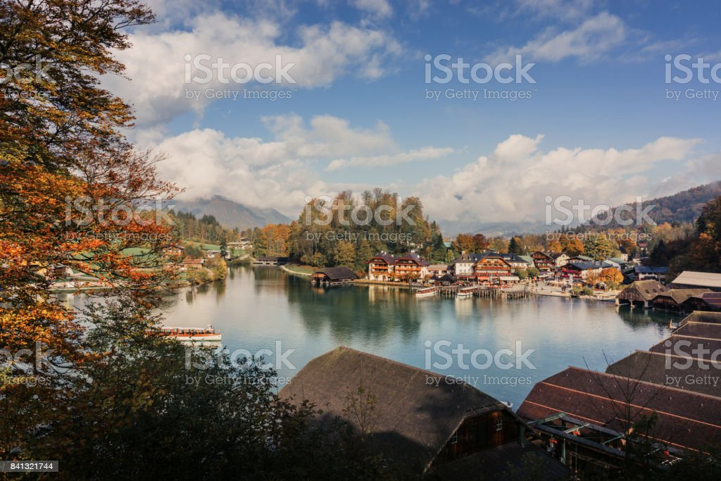 A sightseeing boat cruising on Konigssee ( King's Lake ) surrounded by colorful autumn trees and boathouses on a foggy misty morning~ Beautiful scenery of Bavarian countryside in Berchtesgaden Germany stock photo