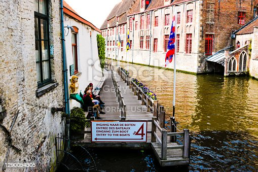 People waiting for a tourist boat to tour the canals of Bruges, a World Heritage town./ Katelijnestraat, Brugge, Belgium/ 05-07-2019
