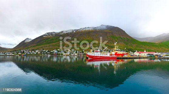 Siglufjörður, Iceland: Trawlers in a fjord harbor in late afternoon in September, with snowcapped green mountains in the background. Siglufjörður is in the Trollaskagi Peninsula in North Iceland, known for its herring industry.