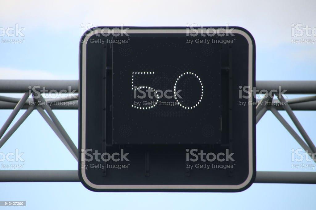 Ondertekenen boven baan met vermelding van de verplichte snelheid in kilometers per uur op Nederlandse snelweg foto