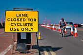During the coronavirus pandemic lockdown, a cyclist approaches a yellow sign advising that a road lane is closed to cars and other traffic and is for cyclists only