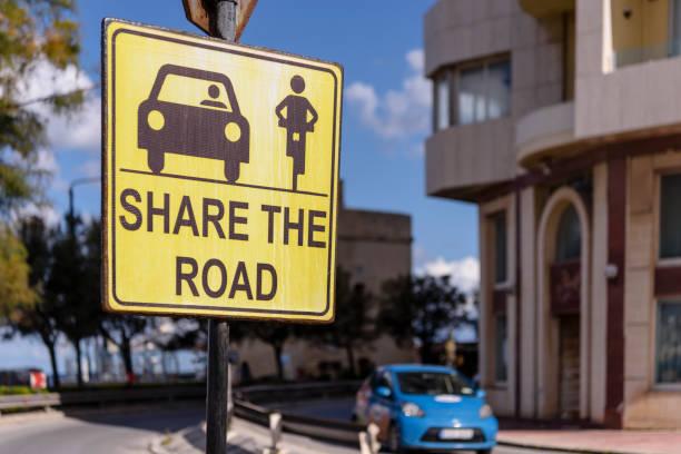 Schild, das den Verkehrsteilnehmern rät, die Straße zwischen Autos und Motorradfahrern zu teilen. – Foto