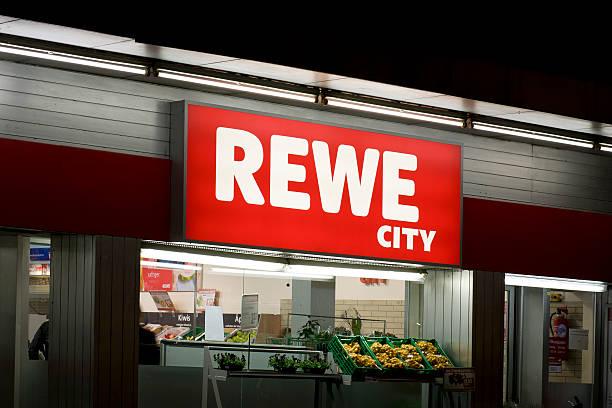 schild und eingang des rewe city supermarkt - rewe germany stock-fotos und bilder