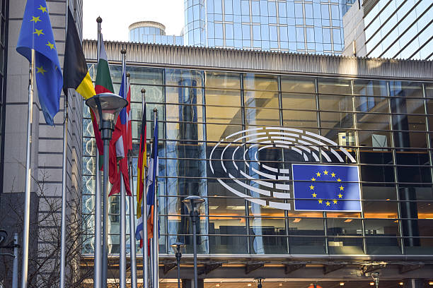 Brussels, Belgium - December 30, 2016: Sign and EU flags Brussels, Belgium - December 30, 2016: Sign and EU flags on glass walls of Berlaymont, that houses the headquarters of the European Commission, which is the executive of the European Union berlaymont stock pictures, royalty-free photos & images