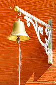 Close up of a metal bell hanging from the wall