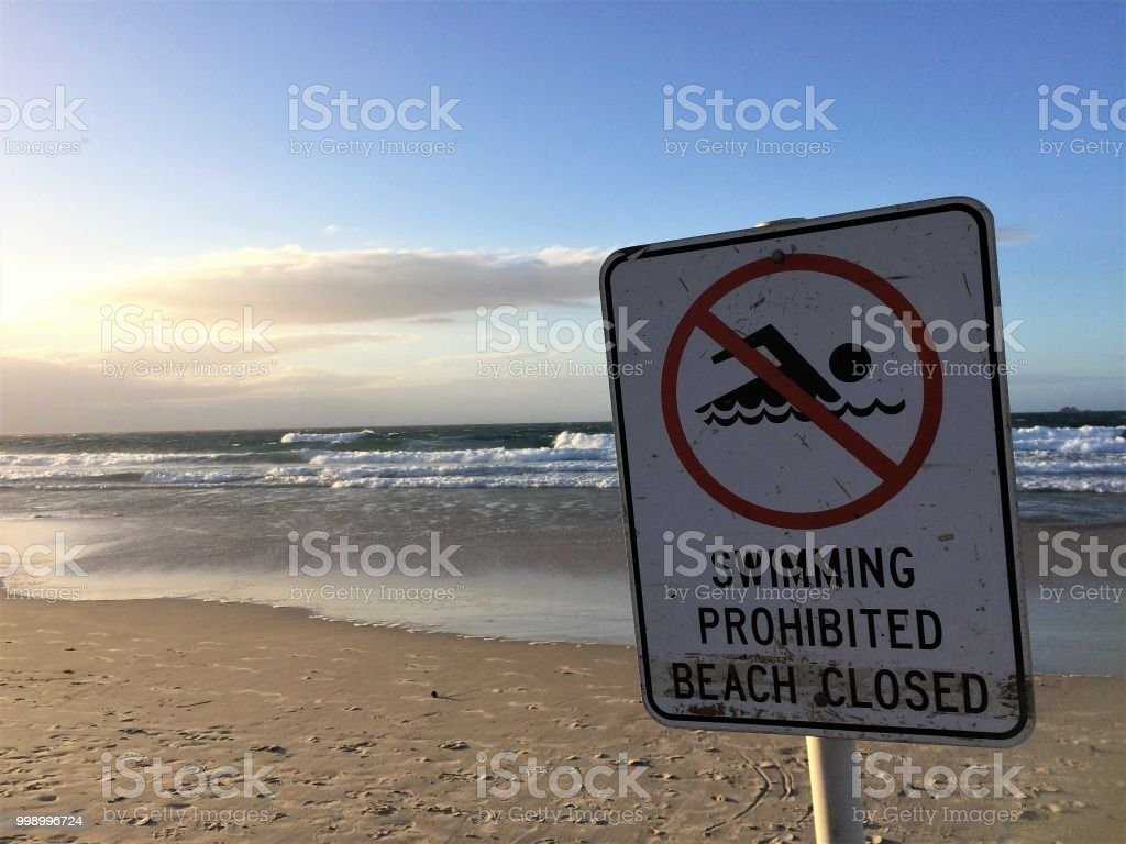 A sign at a beach says that it is closed stock photo