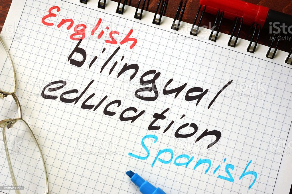 Sign bilingual education written in a notepad on a table. - foto de acervo